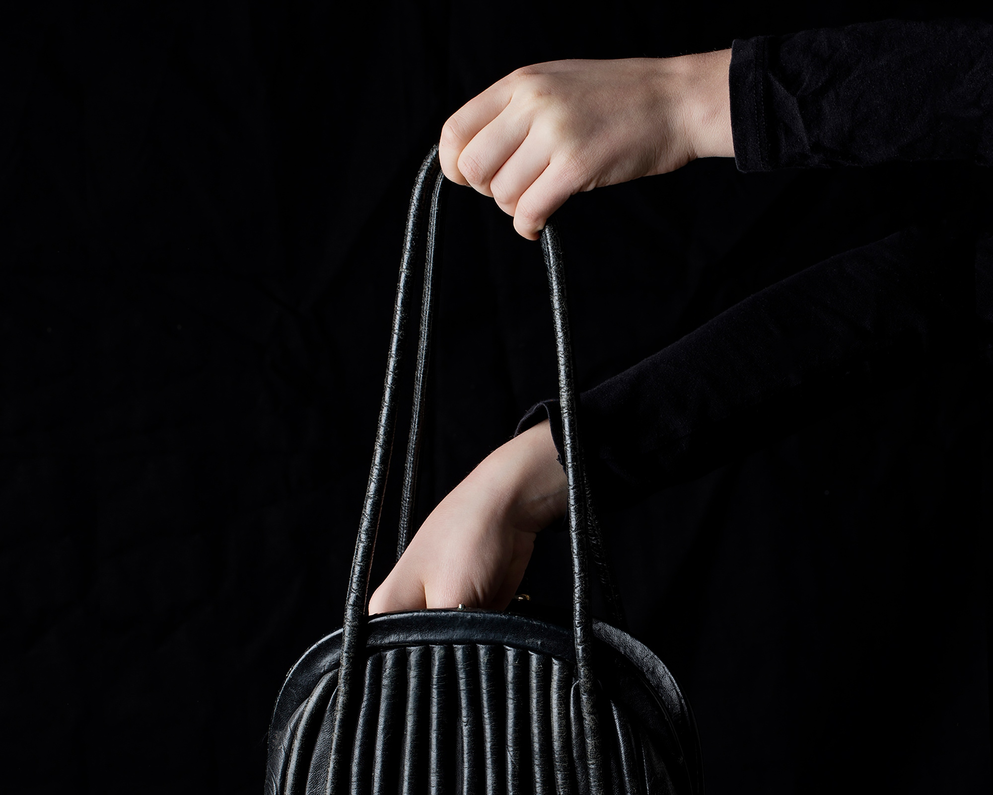 Person holding a handbag and reaching something from the inside of it. Only hands are visible.