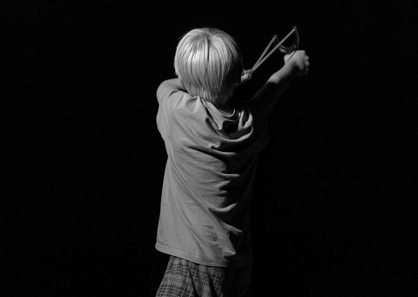 Boy aiming a slingshot