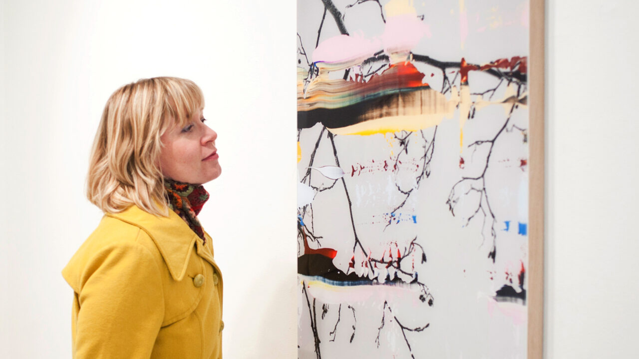 a woman looking at a large photo print on a wall